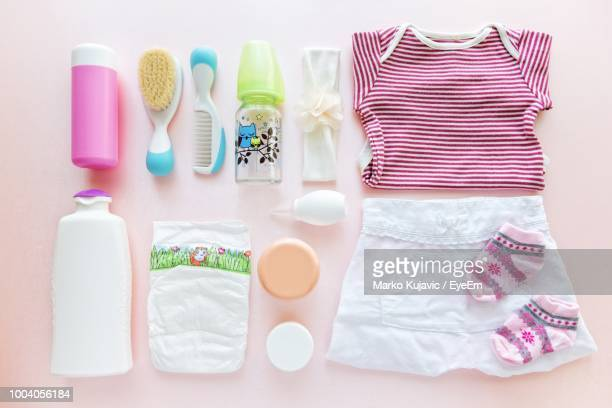 directly above shot of baby clothing with comb and bottle - babybekleidung stock-fotos und bilder