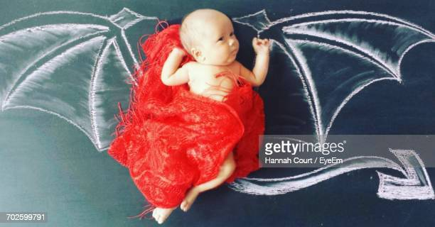 Directly Above Shot Of Baby Girl Lying Amidst Devil Wings Drawn On Blackboard