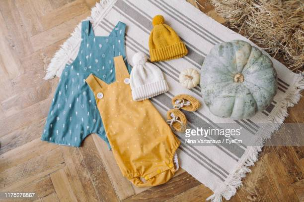 directly above shot of baby warm clothes with pumpkins on hardwood floor - baby clothing stock pictures, royalty-free photos & images