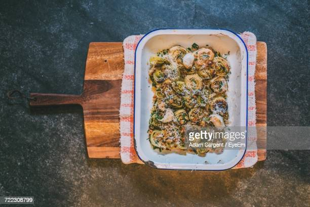 Directly Above Shot Of Baked Leek Rolls In Casserole With Cutting Board And Napkin On Marble