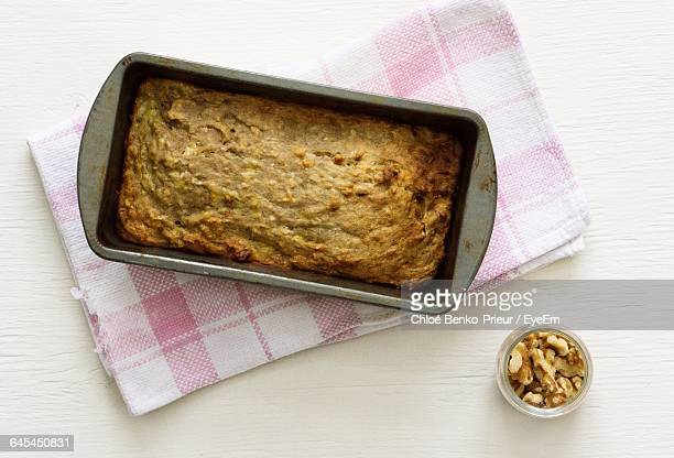 directly above shot of banana bread in container on table - banana loaf stockfoto's en -beelden
