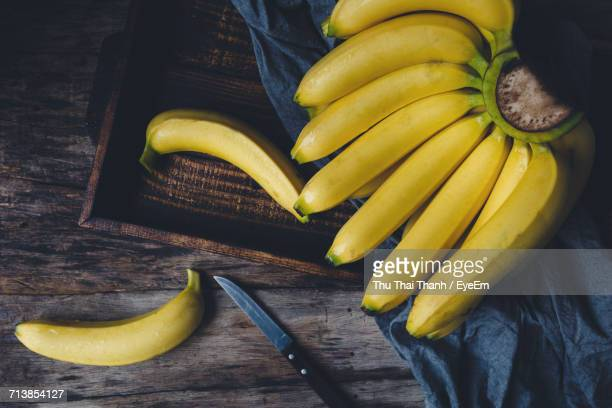 directly above shot of bananas with knife on wooden table - 束 ストックフォトと画像
