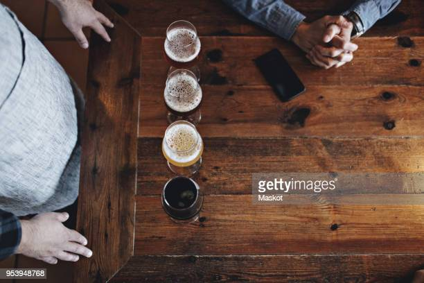 directly above shot of bartender with various beer glasses by customer at wooden table - artisanal food and drink stock pictures, royalty-free photos & images