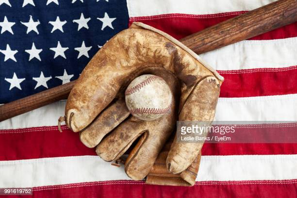 directly above shot of baseball bat with ball and glove on american flag - baseball bat stock pictures, royalty-free photos & images