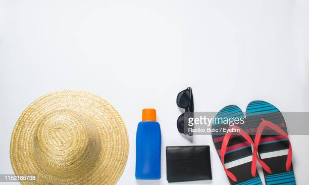 directly above shot of beach supplies on gray background - straw hat stock pictures, royalty-free photos & images