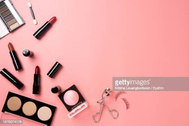 directly above shot of beauty products over peach background - make up stockfoto's en -beelden