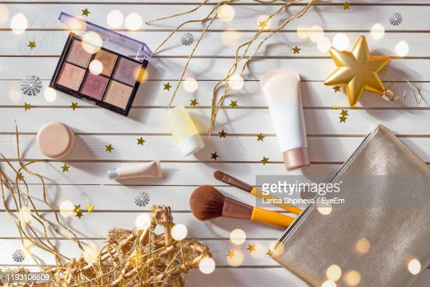 directly above shot of beauty products with christmas decorations on table - cosmetics stock pictures, royalty-free photos & images