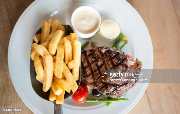 directly above shot of beef steak and french fries in plate on table - fries stock-fotos und bilder