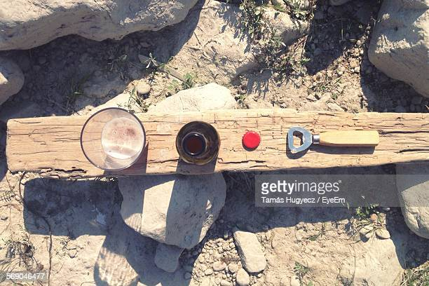 Directly Above Shot Of Beer Bottle And Drinking Glass On Wood At Field