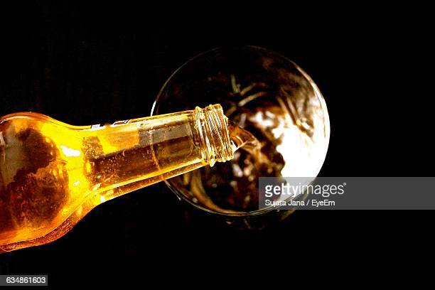 Directly Above Shot Of Beer Pouring From Bottle In Glass Against Black Background