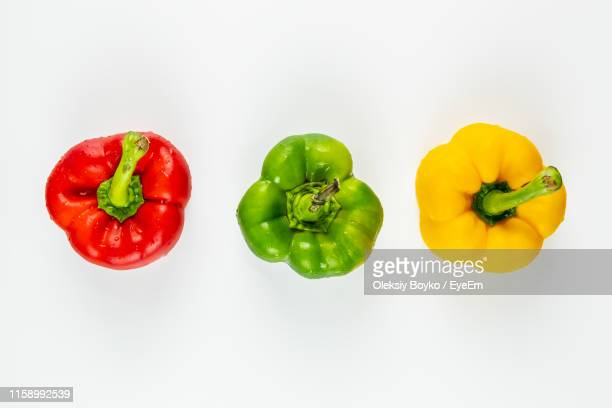 directly above shot of bell peppers against white background - yellow bell pepper stock pictures, royalty-free photos & images