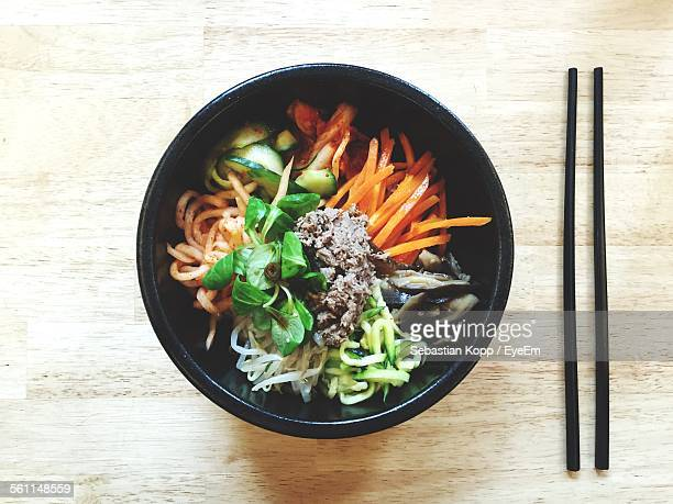 directly above shot of bi bim bap served in bowl on table - korean food stock pictures, royalty-free photos & images