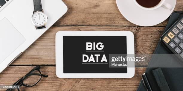 Directly Above Shot Of Big Data Headline On Digital Tablet At Wooden Desk In Office