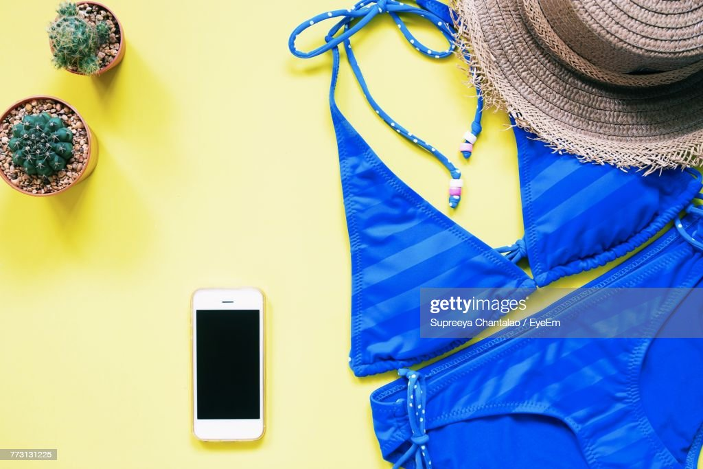 Directly Above Shot Of Bikini And Mobile Phone On Table : Photo