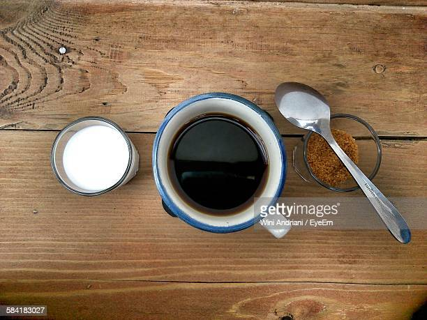 Directly Above Shot Of Black Coffee Amidst Milk And Brown Sugar On Table