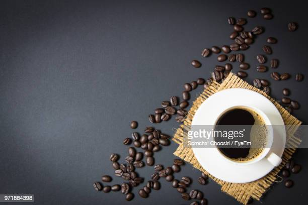directly above shot of black coffee and beans on table - black coffee stock pictures, royalty-free photos & images
