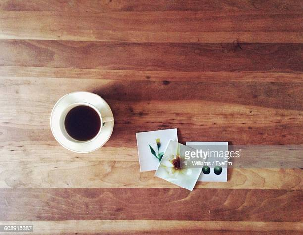 Directly Above Shot Of Black Coffee And Pictures On Wooden Table