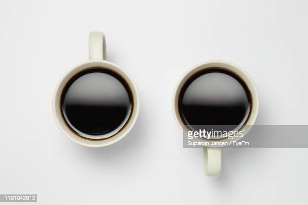 directly above shot of black coffee over white background - two objects stock pictures, royalty-free photos & images