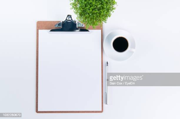 directly above shot of black coffee with clipboard and plants over white background - clipboard stock pictures, royalty-free photos & images