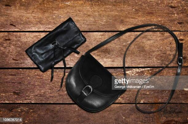 directly above shot of black purse and clutch on table - black purse stock pictures, royalty-free photos & images