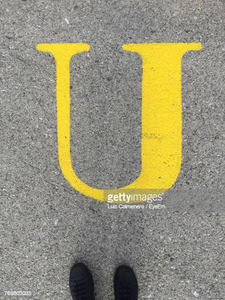 directly above shot of black shoes by letter u on street - letter u stock photos and pictures
