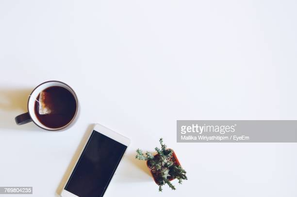 Directly Above Shot Of Black Tea With Smart Phone And Plant On White Background
