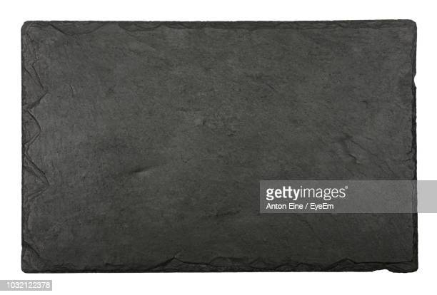 directly above shot of black textured slate over white background - slate rock stock photos and pictures