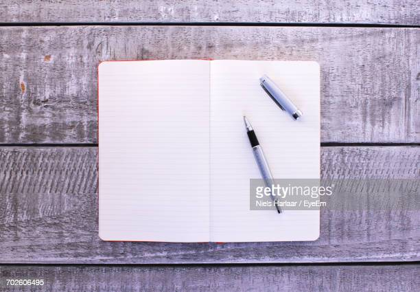 Directly Above Shot Of Blank Book And Pen On Wooden Table