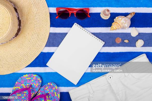 directly above shot of blank book with hat and sunglasses on table - strohoed stockfoto's en -beelden