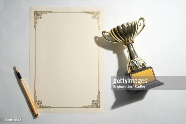 directly above shot of blank certificate with trophy over white background - draft sports stock pictures, royalty-free photos & images