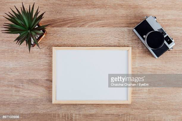 Directly Above Shot Of Blank Frame With Camera And Plant On Wooden Table