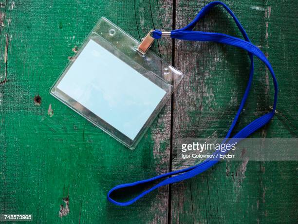 Directly Above Shot Of Blank Id Card On Green Wooden Table