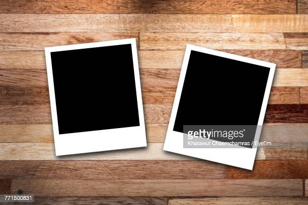 directly above shot of blank instant print transfers on wooden table - two objects stock pictures, royalty-free photos & images