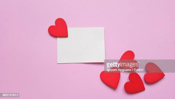 directly above shot of blank paper by red heart shapes on pink background - valentine's day holiday stock pictures, royalty-free photos & images