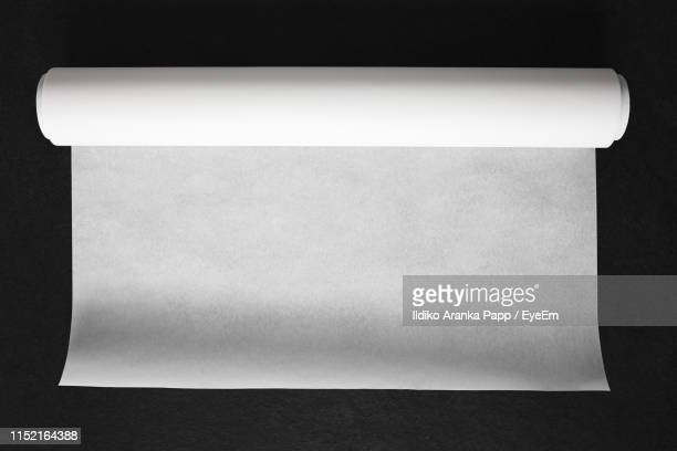 directly above shot of blank paper on black background - rolled up stock pictures, royalty-free photos & images
