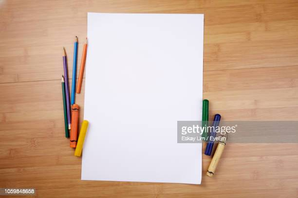 directly above shot of blank paper with crayons and colored pencils on table - crayon stock pictures, royalty-free photos & images