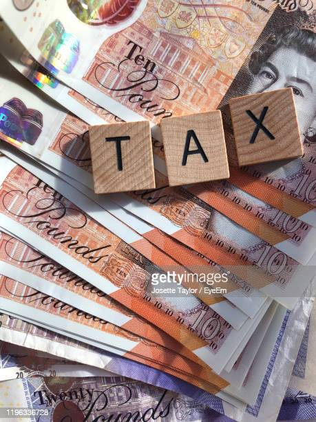 directly above shot of blocks with tax message on paper currency - tax stock pictures, royalty-free photos & images