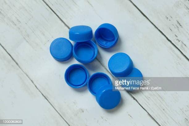 directly above shot of blue bottle caps on table - cap stock pictures, royalty-free photos & images