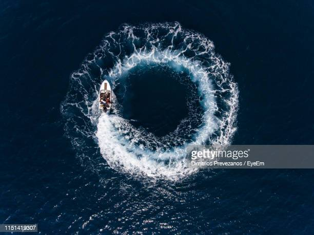 directly above shot of boat making water wake in sea - circle stock pictures, royalty-free photos & images