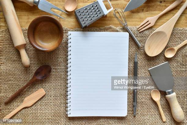 directly above shot of book and kitchen utensils on table - wimol wongsawat stock photos and pictures