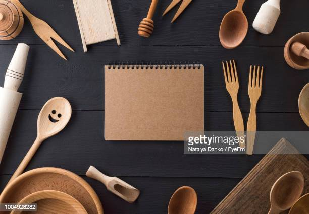 Directly Above Shot Of Book Surrounded With Wooden Kitchen Utensils On Table