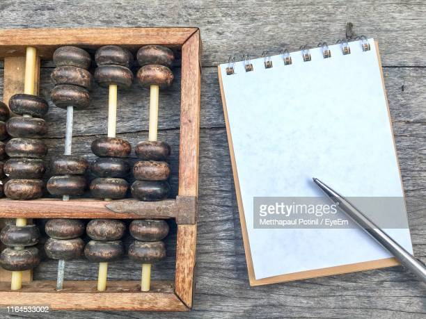 directly above shot of book with abacus on table - metthapaul stock photos and pictures