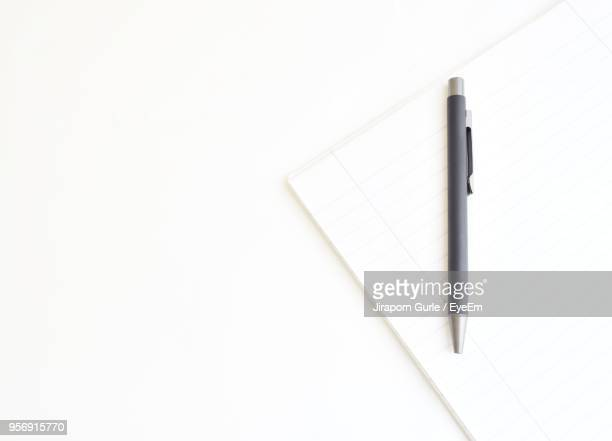 directly above shot of book with pen over white background - stift stock-fotos und bilder