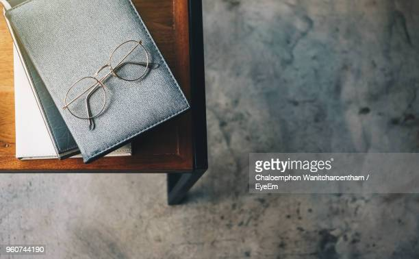 directly above shot of books with eyeglasses on table over marble flooring at home - reading glasses stock pictures, royalty-free photos & images