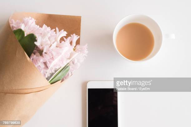 Directly Above Shot Of Bouquet With Tea And Mobile Phone On White Table