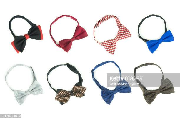 directly above shot of bow ties over white background - 蝶ネクタイ ストックフォトと画像
