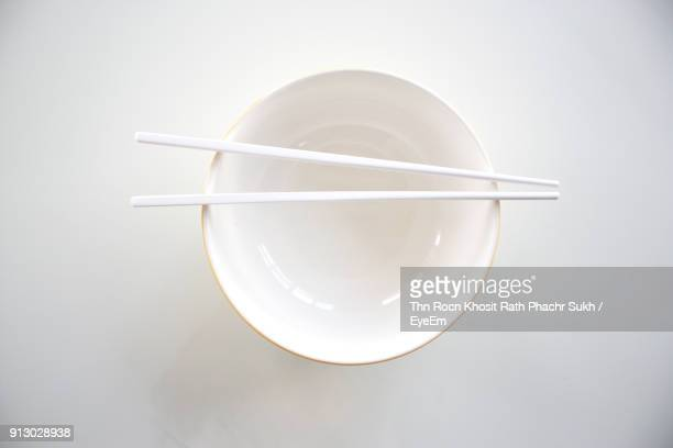 directly above shot of bowl with chopsticks on white background - chopsticks stock pictures, royalty-free photos & images