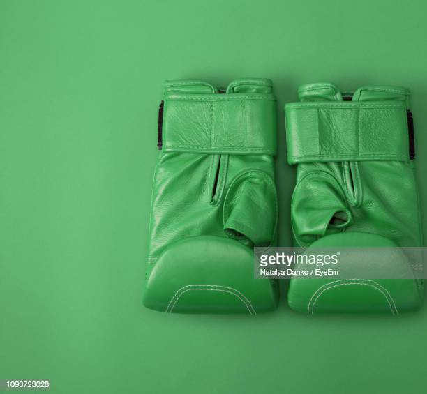 directly above shot of boxing gloves on green background - green glove stock photos and pictures