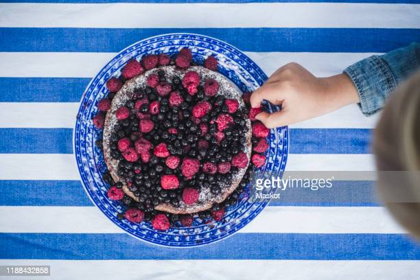 directly above shot of boy picking up raspberry in tart at table - alleen jongens stockfoto's en -beelden