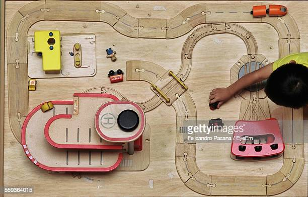 Directly Above Shot Of Boy Playing With Toy Train